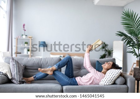 Beautiful smiling woman reading a book and lying on the sofa in the living room. Have a good time at home.