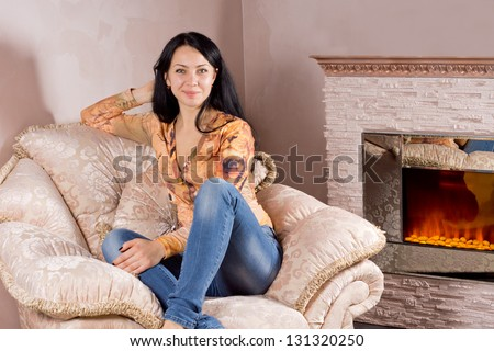 Beautiful smiling woman relaxing in her jeans and stylish top in a comfortable upholstered armchair in front of a warm fire
