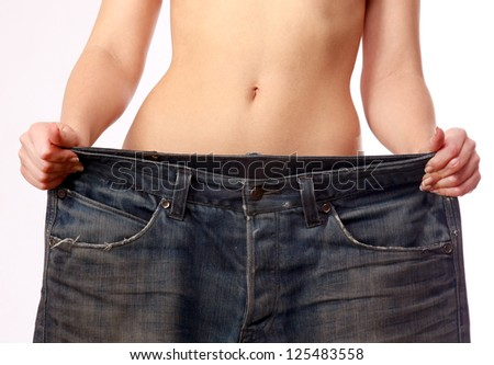 Beautiful smiling woman showing how much weight she lost - Isolated on white