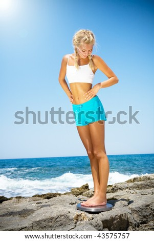 Beautiful smiling woman standing on a scale against blue ocean background.
