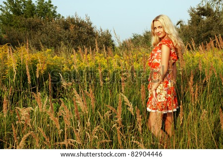 Beautiful smiling woman standing on the field