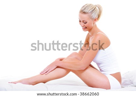 Beautiful smiling woman stroking her beauty legs sitting on the white bed
