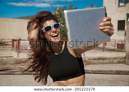Beautiful, smiling woman take a picture of herself with digital tablet. Selfie style. Toned in warm colors. Copy space for your text. Outdoors shot, horizontal.