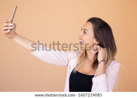 Beautiful smiling woman taking selfie with smartphone. Studio shot of attractive young lady posing for self portrait. Self portrait concept