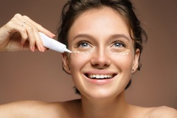 Beautiful smiling woman using cream around the eyes. Photo of woman with perfect skin on brown background. Skin care and beauty