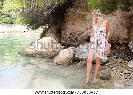 Beautiful smiling woman visiting beach retreat on summer holiday, dipping tip toes in sea water, testing temperature outdoors. Healthy tourist woman relaxing by the sea, wellness recreation lifestyle.