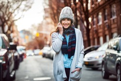Beautiful smiling woman walking on city street wearing casual style clothes