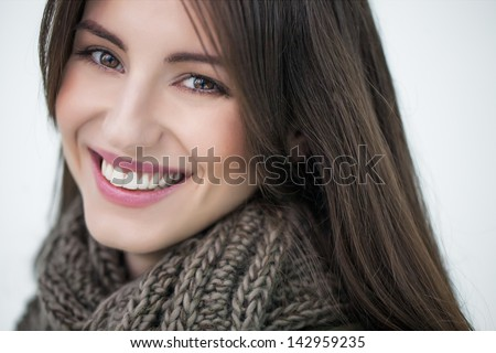 Beautiful smiling woman wearing a warm woolen scarf.