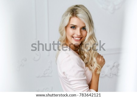 Beautiful Smiling Woman With Blond Hair And Beauty Face. Portrait Of Happy Blonde Girl With Natural Hairstyle And Makeup In Light Interior. High Quality Image.