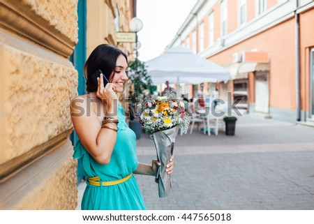 Beautiful smiling woman with bouquet of flowers making a phone call on the street - Shutterstock ID 447565018