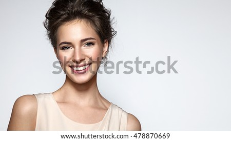 Beautiful smiling woman with clean skin, natural make-up, and white teeth on grey background #478870669
