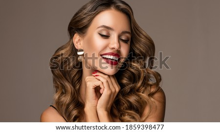 Beautiful smiling woman with long wavy hair .  Girl curly hairstyle  and red manicure nails . Beauty ,makeup and cosmetics .Smile with white and even teeth. Earring jewelry