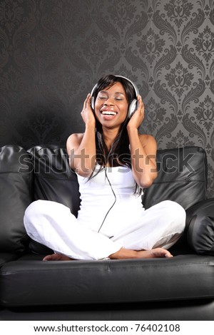 Beautiful smiling young african american woman sitting on black leather sofa at home, headphones on listening to music.