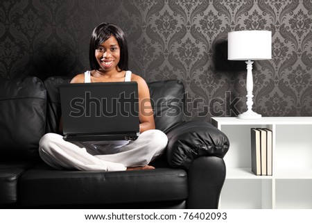Beautiful smiling young black woman sitting cross legged on leather sofa at home, surfing the internet with her laptop computer.