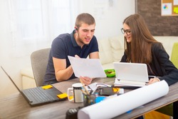 Beautiful smiling young businesswoman sitting working with a young man in a busy office as they discuss about information on a document