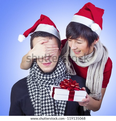 Beautiful smiling young couple celebrating New Year. Attractive woman covering man's eyes with a hand, surprising him with a present