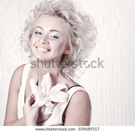 Beautiful smiling young female with original make up, hairdress and flower