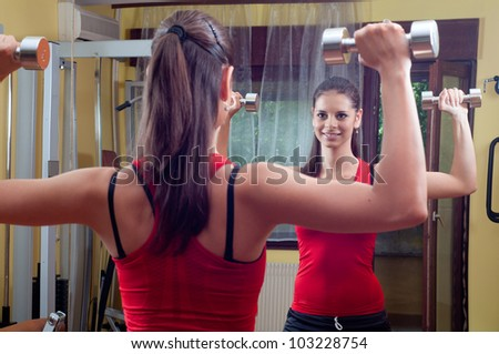 Beautiful smiling young girl exercising in the gym with dumbbells.