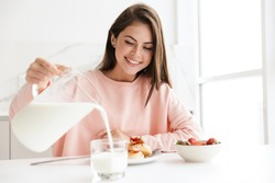 Beautiful smiling young girl having tasty healthy breakfast while sitting at the kitchen table