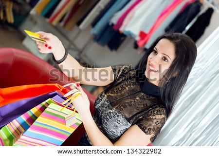 Beautiful smiling young girl shopping with credit card