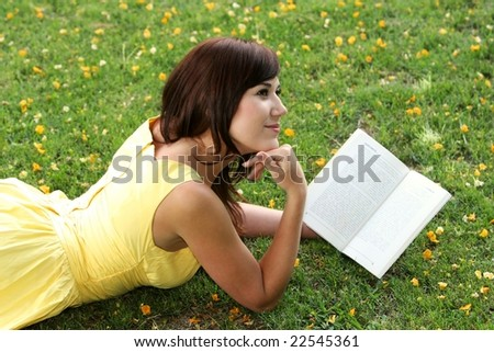 Beautiful smiling young lady reading a book while laying on the grass
