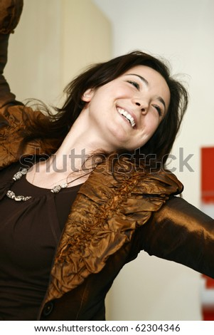 Beautiful smiling young lady with arms raised.\\ Cosmetics, beauty, care products. Happiness, celebration, good luck.