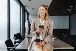 Beautiful smiling young smart businesswoman standing in the office with group of colleagues on the background, using mobile phone