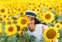 Beautiful smiling young woman in a hat with flower on her eye and face on a field of sunflowers.