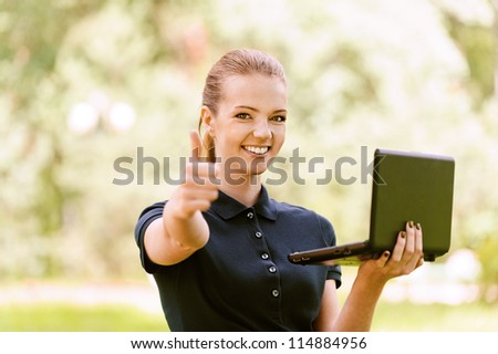 Beautiful smiling young woman in dark blouse keeps your laptop and lifts thumb upwards, against green of summer park.