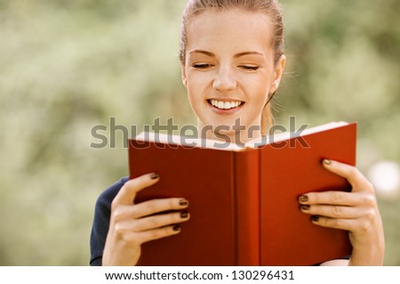 Beautiful smiling young woman in dark blouse reads red book, against green of summer park.