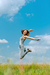 Beautiful smiling young woman jumping, against background of blue sky.