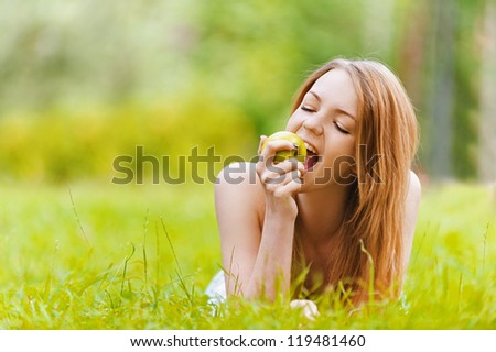 Beautiful smiling young woman lying on grass and bit apple, against background of summer green park.