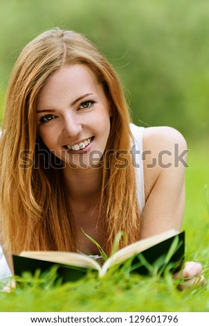 Beautiful smiling young woman lying on grass and reading book, against green of summer park.