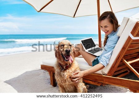 Beautiful Smiling Young Woman Playing With Pet While Using Laptop Computer Outdoors By Sea. Happy Girl Having Fun With Her Dog, Relaxing On Deck Chair At Beach On Summer Holiday Vacations.