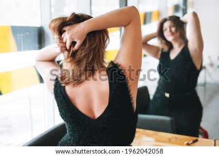 Beautiful smiling young woman plus size body positive in black evening dress make hair style near mirror at beauty studio Photo stock ©