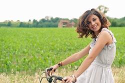 Beautiful smiling young woman portrait with bike in a country road.