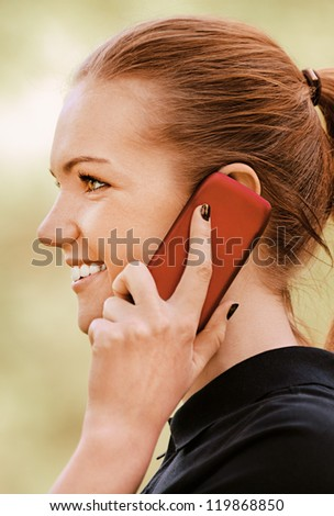 Beautiful smiling young woman profile in dark blouse talking on mobile phone, against green of summer park.