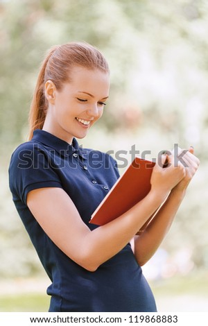 Beautiful smiling young woman reading red book, against background of summer green park.