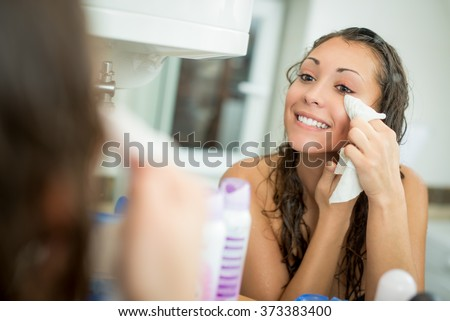 Beautiful smiling young woman removing make up with a facial wipe in front of mirror.