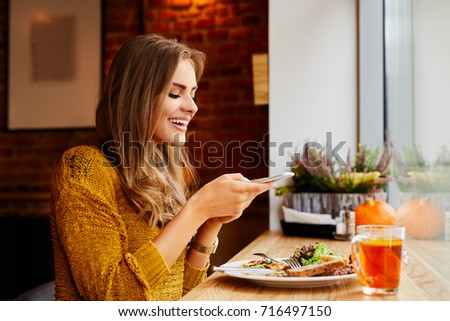 Beautiful smiling young woman sitting in cafe taking photo of her breakfast and laughing