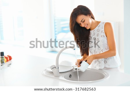 Beautiful smiling young woman washing a cup in white kitchen.
