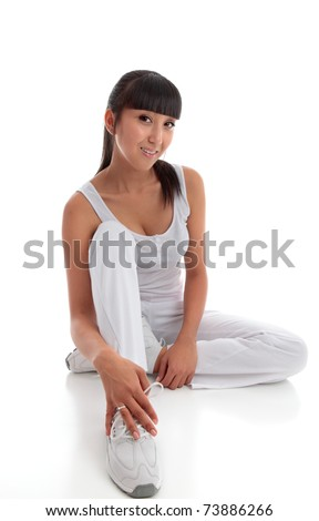 Beautiful smiling young woman wearing white exercise tracksuit pants, sports shoes and tanktop sits on the floor casually.  White background.