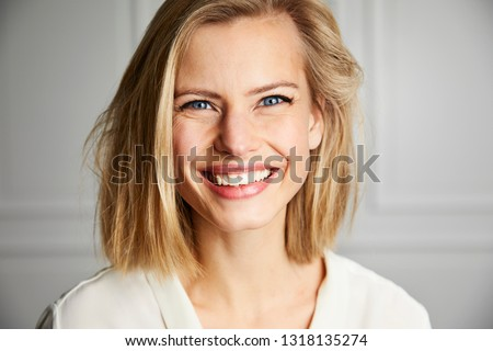 Beautiful smiling young woman with blue eyes, portrait