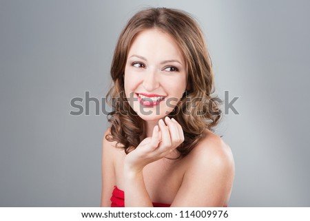 Beautiful smiling young woman with make-up and wavy hairstyle and shiny skin on grey background. Studio shot