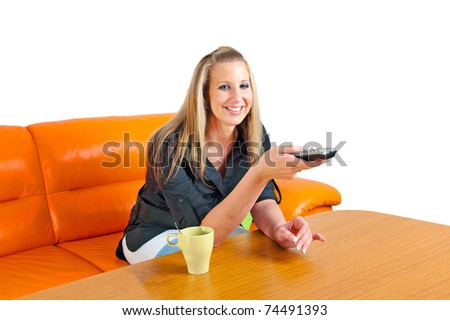 Beautiful smiling young woman with remote control on a sofa in her living room