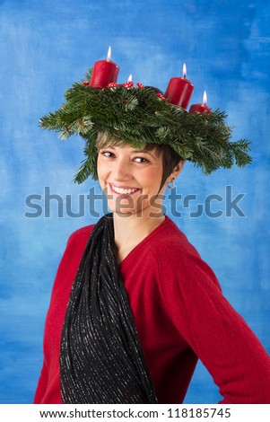 Beautiful smiling young woman woman wearing advent wreath on her head, four candles are burning. Studio shot with copy space against a blue background, series
