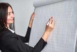 Beautiful smiling young woman writing on a blank flipchart in office as she does a presentation or promotion