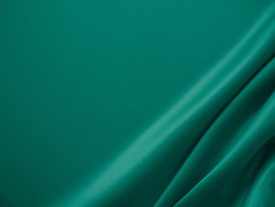 Beautiful smooth elegant wavy emerald green satin silk luxury cloth fabric texture, abstract background design. Card or banner.