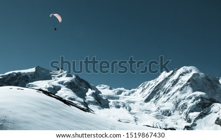 Beautiful snow-capped mountain view with paraglider. Paragliding in Swiss alps Matterhorn region, Switzerland. Concept of extreme sport, taking adventure/ challenge.