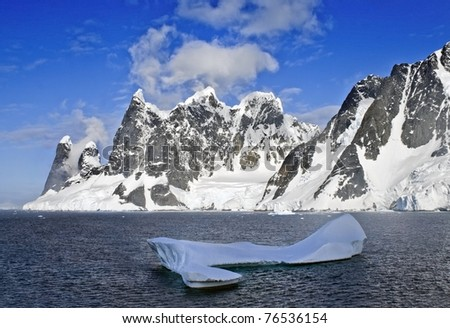 Beautiful snow-capped mountains at with iceberg. Taken at Lemaire Channel, Antarctica.